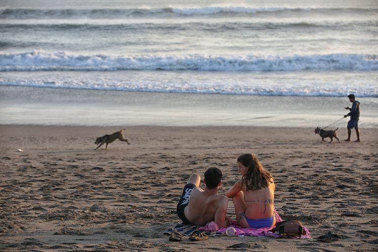 Wisatawan menikmati senja di Pantai Seminyak, Badung, Bali, Senin (22/7/2019). Pantai Seminyak menjadi salah satu lokasi favorit wisatawan untuk menyaksikan matahari terbenam.