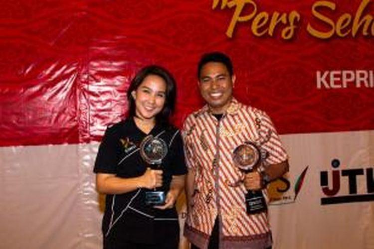 Fotografer Kompas.com Roderick Adrian Mozes (kiri) bersama reporter Kompas TV Mercylia Marlisa Tirayoh menerima Piala Adinegoro dalam acara puncak Hari Pers Nasional di Batam, Senin (9/2/2015).