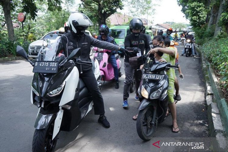 Warga Kota Bogor pengendara sepeda motor melanggar aturan PSBB, tidak menggunakan helm dan masker, diberikan masker oleh petugas pada saat sosialisasi penerapan PSBB di Kota Bogor. (ANTARA/HO/Pemkot Bogor)