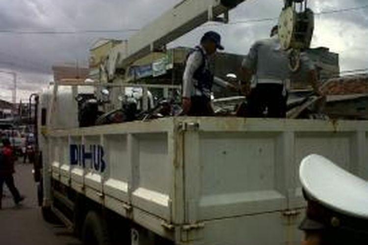 Petugas Dinas Perhubungan DKI Jakarta mengangkut lima sepeda motor diparkir di Jalan KH Mas Mansyur, Tanah Abang, Jakarta Pusat, Senin (6/1/2014). Razia ini dilakukan terkait masih maraknya parkir liar di kawasan niaga tersebut.