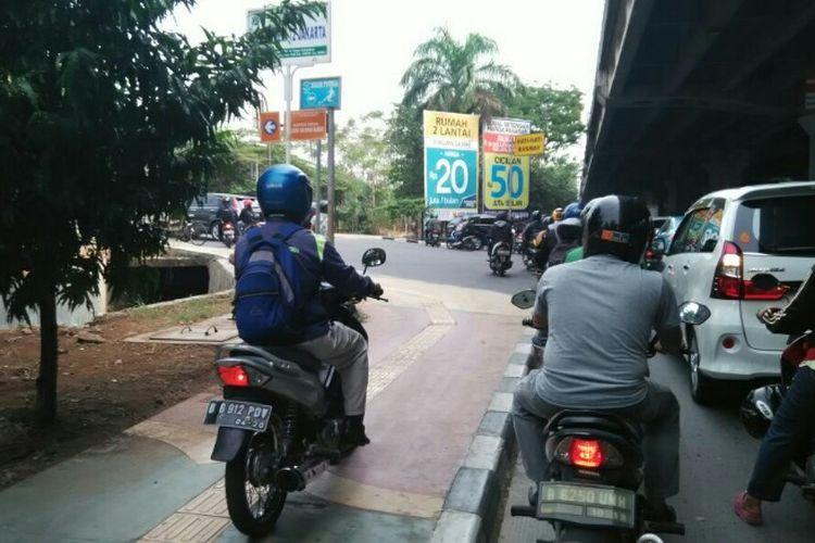 Pengendara motor nekat menaiki trotoar di Jalan Yos Sudarso, Jakarta Utara, Senin (11/9/2017).