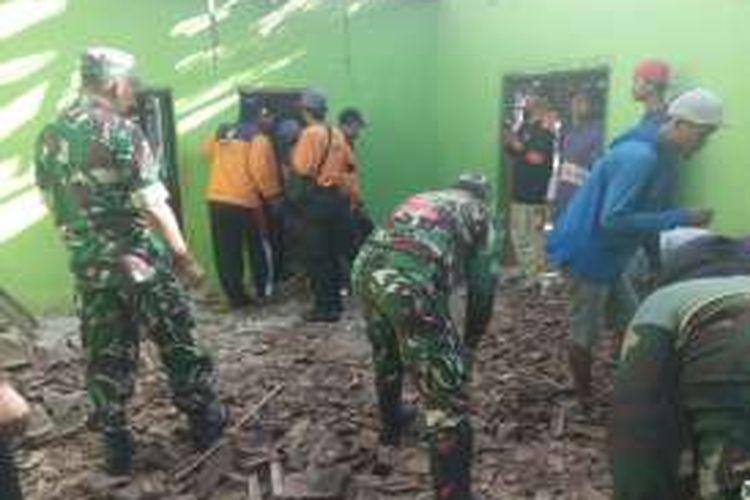 Foto : Aparat TNI AD Koramil Dagangan Kabupaten Madiun membantu membersihkan reruntuhan rumah milik Mulyono yang roboh.