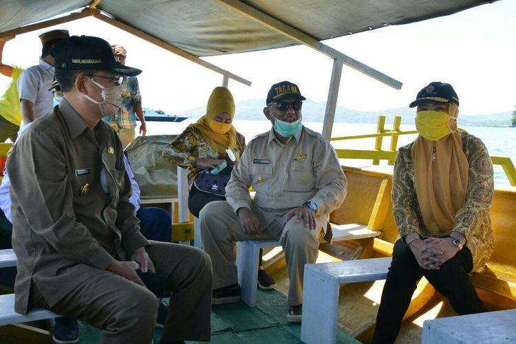 Gubernur Gorontalo, Rusli Habibie (kedua dari kanan) saat berada di perahu menuju ke Kecamatan Kepulauan Ponelo untuk membagikan sembako bagi 1300 keluarga kurang mampu di lokasi tersebut, Selasa (28/04/2020).