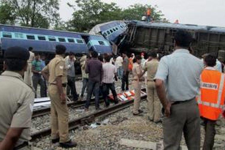 Polisi dan petugas kereta api India, memeriksa puing-puing gerbong KA Gorakhpur Express yang bertabrakan dengan sebuah kereta barang yang sedang parkir di sebuah stasiun di negara bagian Uttar Pradesh.