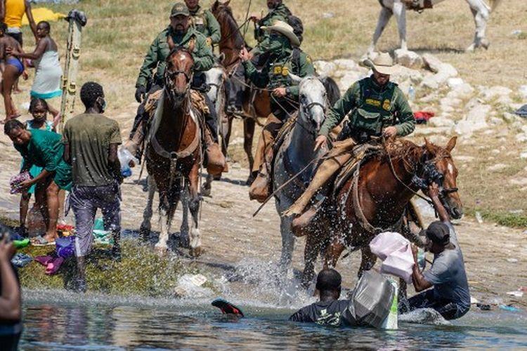 Agen Patroli Perbatasan Amerika Serikat yang menunggang kuda mencoba untuk menghentikan migran Haiti memasuki perkemahan di tepi Rio Grande dekat Jembatan Internasional Acuna Del Rio di Del Rio, Texas pada 19 September 2021.