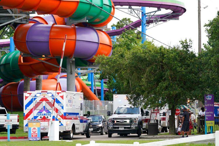 Kendaraan personel darurat diparkir di dekat tempat orang dirawat setelah kebocoran bahan kimia di Six Flags Hurricane Harbour Splashtown Sabtu, 17 Juli 2021 di Spring, Texas.