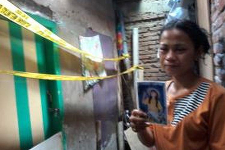 Saat ditemui di depan rumahnya, Kamis (9/7/2015), Ani memperlihatkan foto almarhumah anaknya, TR alias M (12) yang tewas dibunuh ayah kandungnya, Rudi Khaeruddin.