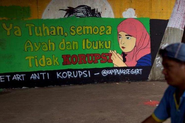 Penjual minuman keliling melintas didepan mural berisi kritikan terhadap koruptor di Jalan Gatot Subroto, Jakarta Selatan, Rabu (12/12/2012). Kritikan terhadap pelaku koruptor terus disuarakan oleh aktivis untuk mendorong tindakan lebih tegas dalam pemberantasan korupsi dan penegakan hukum lainnya.
