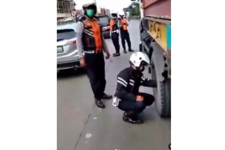 Tangkapan layar video yang menampilkan seorang petugas dinas perhubungan (dishub) mengempesi ban truk di Cibitung, Jumat (8/1/2021).