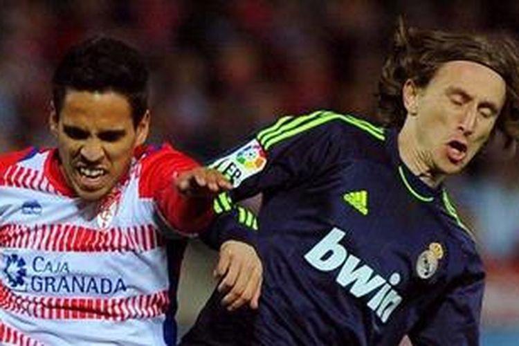 Gelandang Granada, Jose Luis Recio (kiri), berebut bola melawan gelandang Real Madrid dari Kroasia, Luka Modric, dalam laga Liga BBVA di Stadion Nuevo Los Carmenes, Sabtu (2/2/2013).