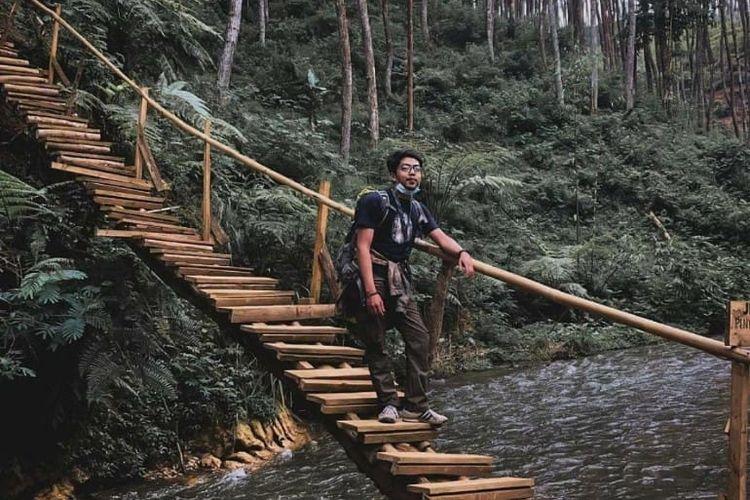 Pengunjung berfoto di jembatan di atas Sungai Palayangan di area Wisata Kampung Singkur