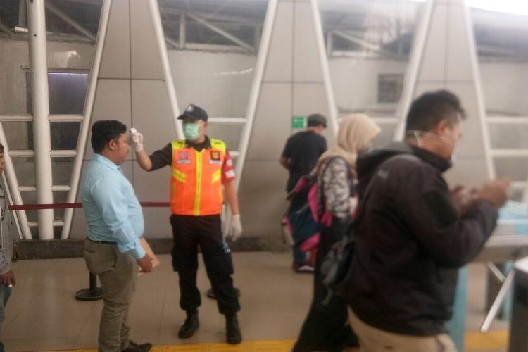 Petugas sedang melakukan pengecekan suhu tubuh terhadap para calon penumpang KRL di Stasiun Bogor, Senin (16/3/2020).