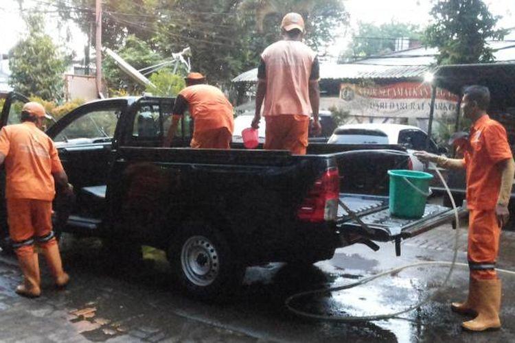 Sejumlah petugas pemeliharaan prasana dan sarana umum (P3SU) Kelurahan Jatinegara yang tengah membersihkan mobil pengangkut sampah di halaman Kantor Kelurahan Jatinegara, Cakung, Jakarta Timur, Senin (23/1/2017)