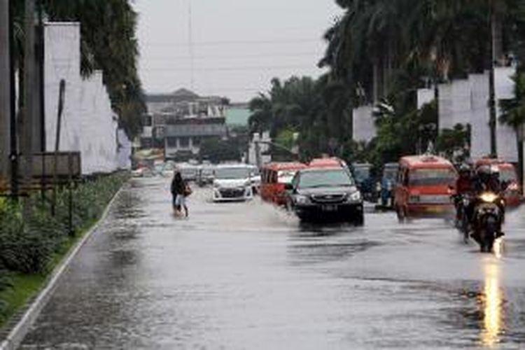 Pengendara melintasi genangan di Jalan boulevard, Kelapa Gading  Jakarta Utara, Jumat (17/1/2014). Hujan lebat mengguyur Jakarta sejak pagi, membuat sejumlah jalanan Ibukota tergenang.