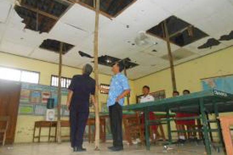 Guru SD Negeri 2 Doreng, Kecamatan Wonosalam, Demak, menunjukan atap ruang kelas yang rusak, Selasa (7/4/2015)