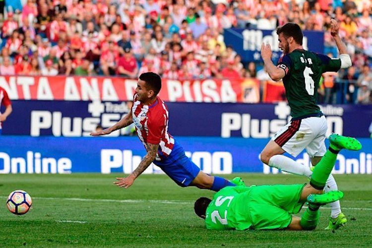 Pemain Atletico Madrid, Yannick Ferreira Carrasco, dijatuhkan kiper Osasuna, Salvatore Sirigu, pada pertandingan Divisi Primera La Liga Spanyol di Stadion Vicente Calderon, Sabtu (15/4/2017).