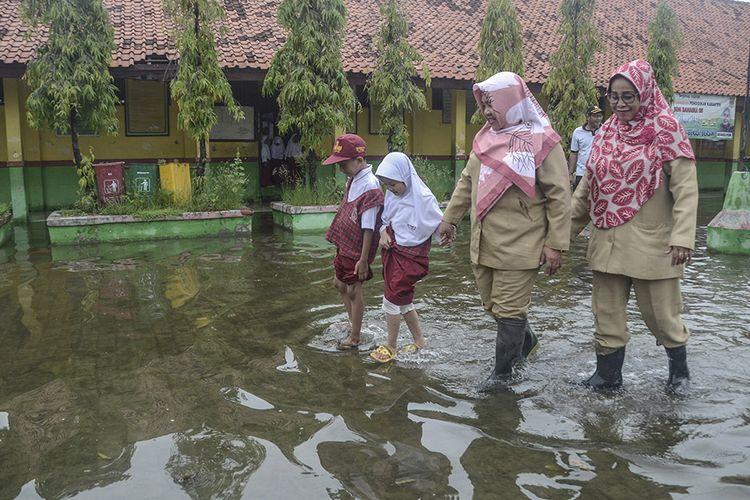 Sejumlah guru dan murid SDN 05 beraktivitas saat banjir di daerah Pondok Ungu, Kabupaten Bekasi, Jawa Barat, Senin (6/1/2020). Hari pertama sekolah terjadi banjir sejak pukul 05.00 pagi akibat luapan kali.