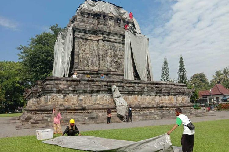 Plastik atau terpaulin yang menutup Candi Mendut, Kabupaten Magelang, Jawa tengah, telah dibuka oleh petugas Balai Konservasi Borobudur (BKB). Proses pembukaan petugas dibantu warga sekitarnya, pada Jumat (16/4/2021)