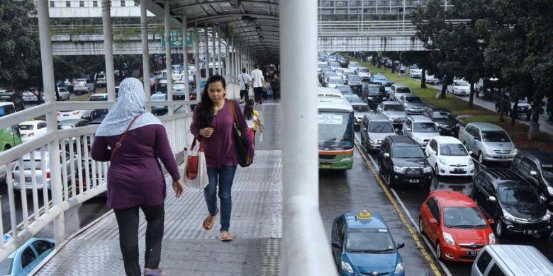 Penumpang berjalan di jembatan penyeberangan usai sampai di Halte Dukuh Atas, Jakarta Selatan, Kamis (11/4/2013). Pembenahan sarana angkutan umum mendesak dilakukan untuk mencegah lalu lintas Jakarta macet total.