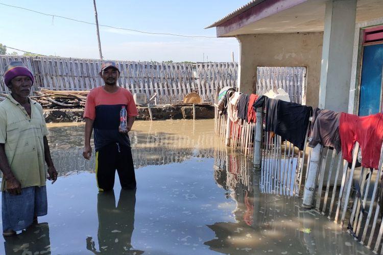 Samsudin (36) warga RT 1, RW 3 Kelurahan Muarareja, Tegal Barat, Kota Tegal, bersama tetangganya kembali ke rumahnya dari pengungsian untuk mengambil sejumlah barang di tengah terjangan air rob, Kamis (4/6/2020)
