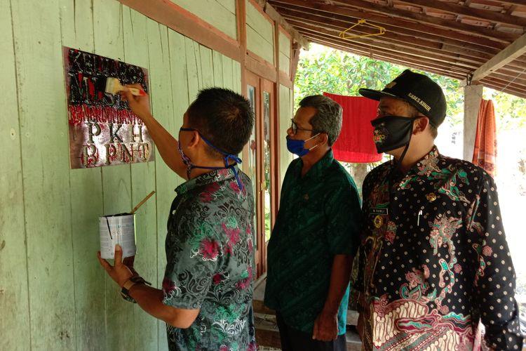 Perangkat Desa Kunir Kecamatan Dempet Kabupaten Demak Jawa Tengah melakukan pengecapan tanda PKH di rumah rumah yang terdata sebagai keluarga miskin , Selasa (5/5/2020)