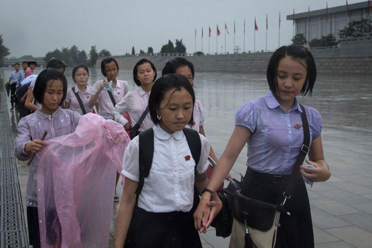 Para pelajar di Pyongyang, Korea Utara berjalan menembus hujan untuk memberikan penghormatan kepada kepada pemimpian Korut Kim Il-Sung dan Kim Jong-Il di luar Istana Kumsusan. Ritual ini mereka lakukan dalam rangka memperingati Hari Kemenangan  yang jatuh setiap tanggal 27 Juli.