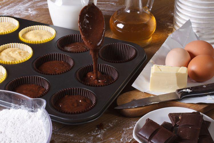 Ilustrasi adonan cupcake cokelat dituang ke loyang. Siap untuk dipanggang.