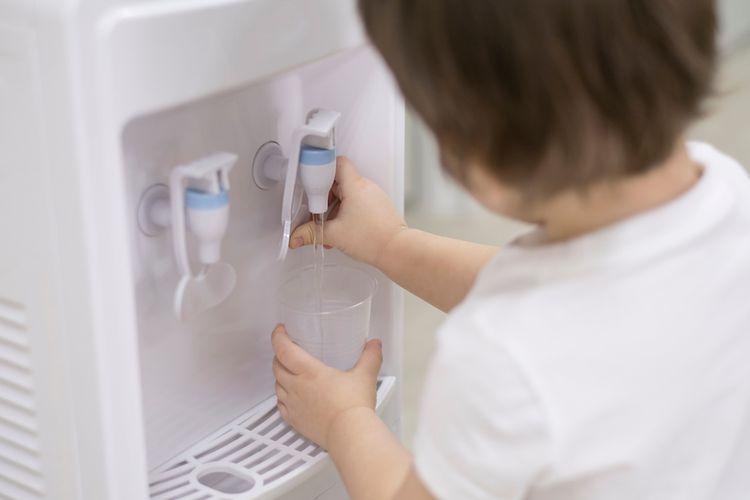 Ilustrasi seseorang tengah mengambil air mineral dari dispenser air.