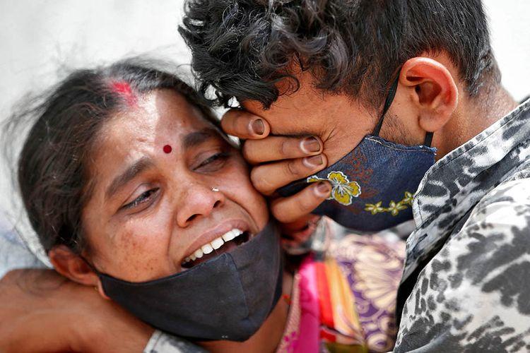 Seorang perempuan berduka dengan anak lelakinya setelah suaminya meninggal dunia akibat penyakit virus corona (Covid-19) di luar kamar mayat rumah sakit Covid-19 di Ahmedabad, India, Selasa (20/4/2021). India dihantam kengerian dengan lonjakan kasus Covid-19 mencetak rekor tertinggi dunia melampaui 17 juta kasus.
