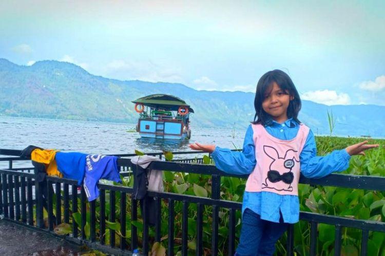 Seorang anak berfoto dengan latar belakang danau dan kapal di Dermaga Dedalu, Desa Dedalu, Kecamatan Lut Tawar, Kabupaten Aceh Tengah