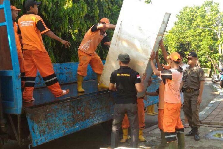 Petugas PPSU membantu warga Bukit Duri pindah ke rusun relokasi, Minggu (18/6/2017).