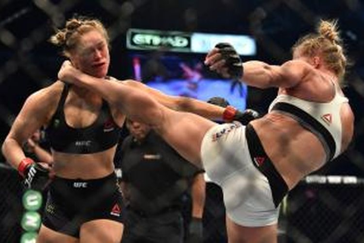 Petarung UFC asal Amerika Serikat, Holly Holm (kanan), menendang bagian kepala sesama petarung AS, Ronda Rousy, pada pertarungan kelas bantam di Melbourne, Australia, Minggu (15/11/2015). Holm menang KO.