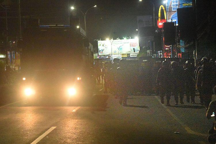 Sejumlah personel Polisi anti Huru-hara (PHH) Polda Banten berbaris di samping kendaraan taktis water cannon untuk menyisir dan membubarkan massa saat unjuk rasa menolak pengesahan Omnibus Law Undang-undang Cipta Kerja di Ciceri di Serang, Rabu (6/10/2020) malam. Polisi membubarkan para demonstran karena bertindak anarkis memblokade jalan protokol hingga larut malam dan melempari petugas dengan batu dan petasan.