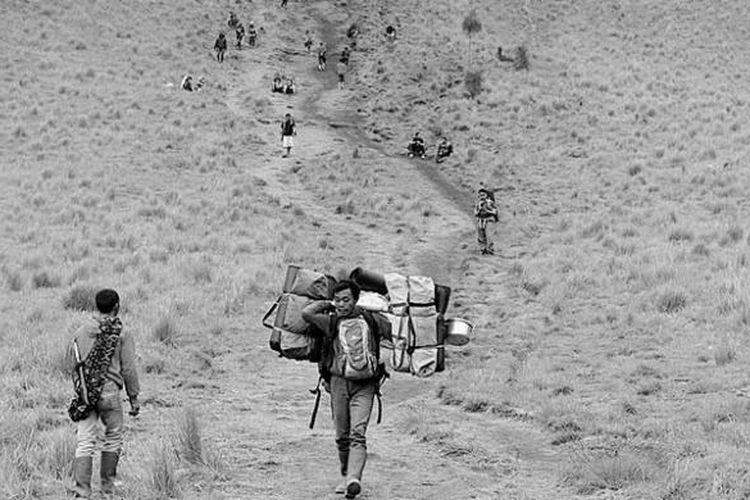 Porter berjalan menuruni Tanjakan Cinta di kawasan Gunung Semeru, Jawa Timur, Selasa (31/12/2013). Para porter yang tinggal di sekitar Semeru turut kecipratan berkah dengan kedatangan ratusan pendaki yang merayakan pergantian tahun di gunung berketinggian 3.676 meter di atas permukaan laut tersebut.