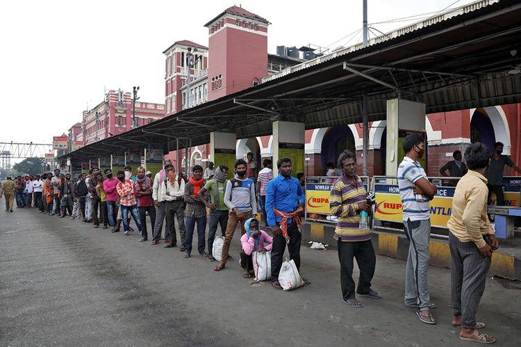 Para pekerja migran menunggu dalam antrean untuk menerima makanan gratis di luar stasiun kereta Howrah setelah Pemerintah India memerintahkan lockdown nasional untuk membatasi penyebaran penyakit virus corona (COVID-19), di Kolkata, India, Rabu (25/3/2020).