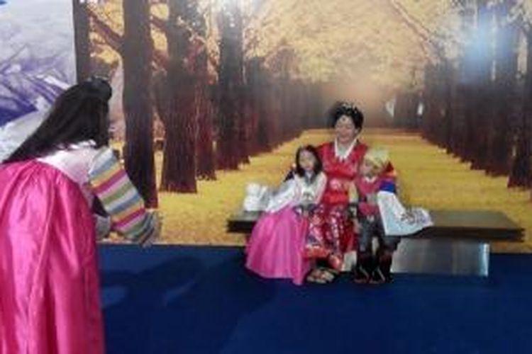 Pengunjung pameran pariwisata Provinsi Gangwon, Korea Selatan, di Jakarta, Jumat (1/5/2015), berfoto dengan busana tradisional Korea, hanbok.