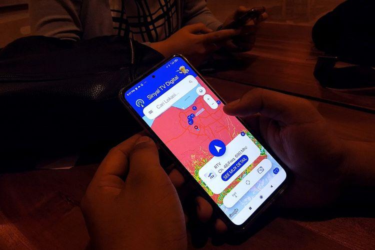 Seorang pria melakukan pengecekan kekuatan sinyal TV Digital melalui aplikasi sinyalTVdigital. Saat membuka aplikasi dapat terlihat sinyal terkuat berasal dari MUX yang mana.