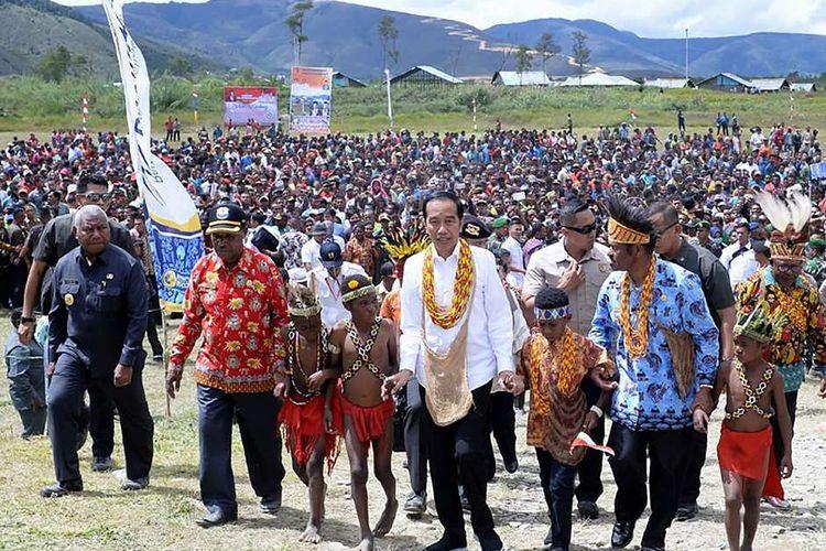 Presiden Joko Widodo (Jokowi) menerima sambutan dari warga Kabupaten Pegunungan Arfak, Papua Barat, saat melakukan kunjungan, Minggu (27/10/2019). Kunjungan ini menjadi kunjungan kerja pertama Jokowi pascapelantikan dirinya sebagai presiden terpilih periode 2019-2014, 20 Oktober lalu.