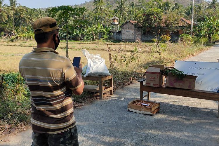Warga blokade jalan masuk salah satu RT di Pedukuhan Tlogolelo, Kalurahan Hargomulyo, Kapanewon Kokap, Kabupaten Kulon Progo, Daerah Istimewa Yogyakarta. Warga meletakkan logistikdi pintu jaga  untuk keluarga yang menjalani isolasi.