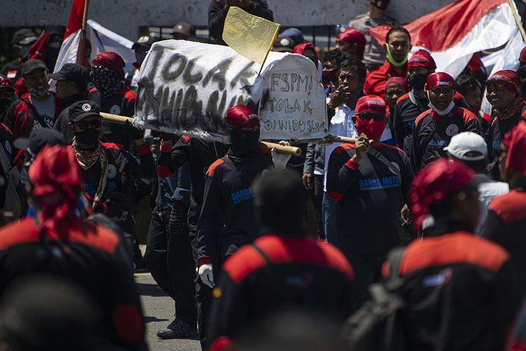 Sejumlah buruh mengangkat replika keranda di depan kompleks Parlemen, Senayan, Jakarta, Selasa (25/8/2020). Dalam aksinya itu ribuan buruh menolak omnibus law draf pemerintah dan menuntut agar PHK massal dampak COVID-19 dihentikan.