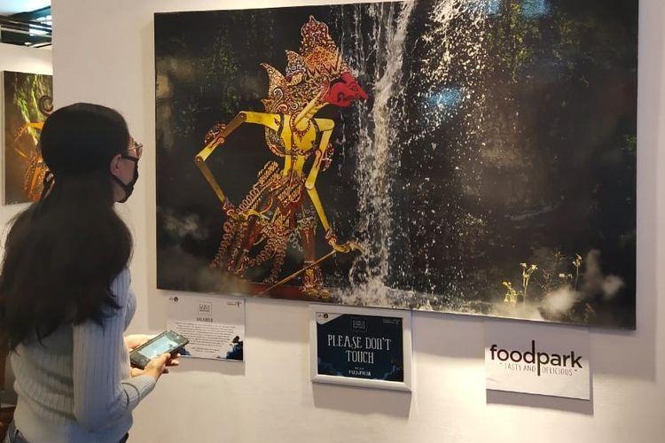 Seorang Pengunjung menyaksikan salah satu karya Fauzie Helmy dalam pameran fotografi Dunia Semata Wayang di The Park, Solo Baru, 6-7 November 2020. (Foto: Fauzie Helmy)