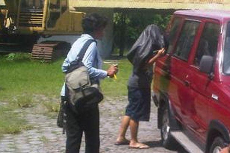 Pelaku (ditutupi jaket) diringkus petugas, Selasa (6/1/2014).