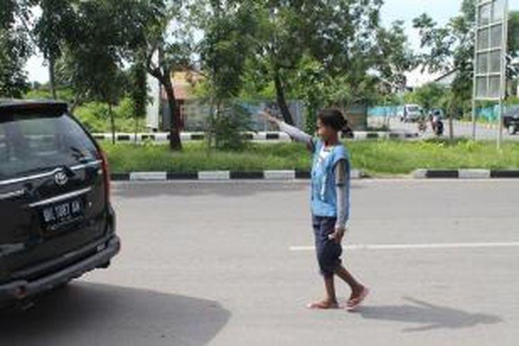 Anita Tamonob (40) satu-satunya tukar parkir perempuan di Kota Kupang, Nusa Tenggara Timur (NTT), sedang menjalankan tugas di tempat kerjanya di depan Rumah Makan Rau Gurih, jalan Eltari Kota Kupang