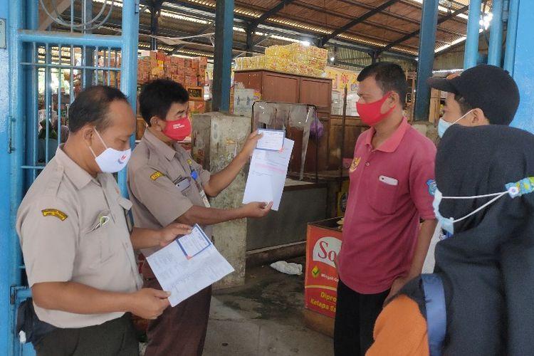Petugas Pasar Langon, Tegal Timur, Kota Tegal memeriksa surat keterangan vaksin bagi pengunjung pasar di tengah diberlakukannya Kota Tegal sebagai kawasan wajib vaksin, Senin (2/7/2021).