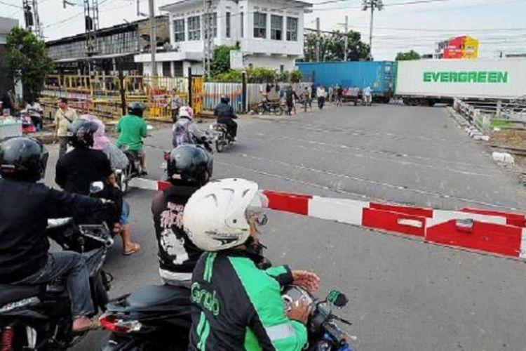 Pengendara sepeda motor berhenti di pintu pelintasan kereta api sebidang Pasar Senen, Jakarta Pusat, Selasa (27/9). Uji coba penutupan pelintasan kereta api sebidang di Pasar Senen mulai diberlakukan pada 1 Oktober.