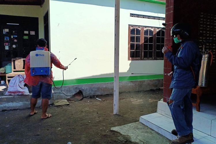 Perangkat desa bersama warga menyemprotkan cairan disinfektan pada fasilitas umum, sekolah, rumah warga guna mencegah penyebaran virus Corona (Covid-19) di Desa Panggungharjo, Sewon, Bantul, Yogyakarta, Minggu (22/3/2020).