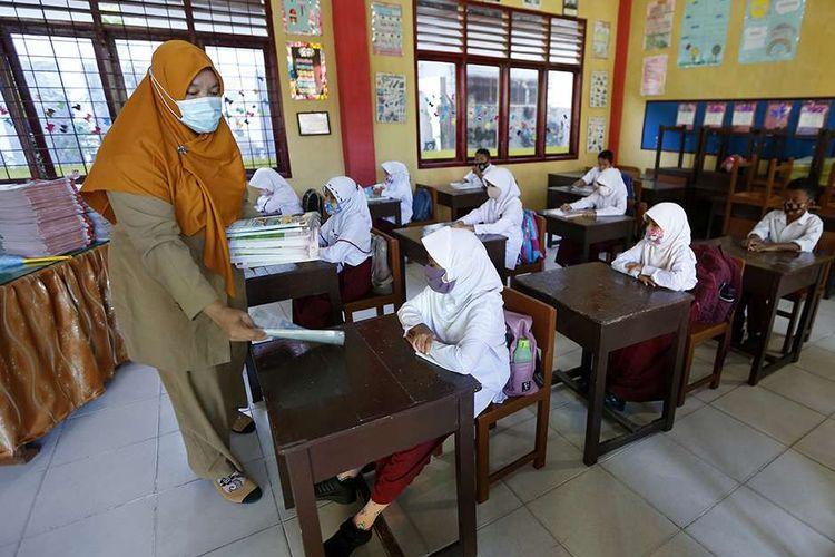 Guru membagikan buku pelajaran kepada pelajar pada hari pertama sekolah tatap muka di SD Negeri 42, Banda Aceh, Aceh, Senin (4/1/2021). Mayoritas lembaga pendidikan tingkat SD, SMP dan SMA di provinsi Aceh mulai melaksanakan pembelajaran tatap muka dengan sistim bergiliran dan menerapkan protokol kesehatan secara ketat untuk mencegah penularan Covid-19.