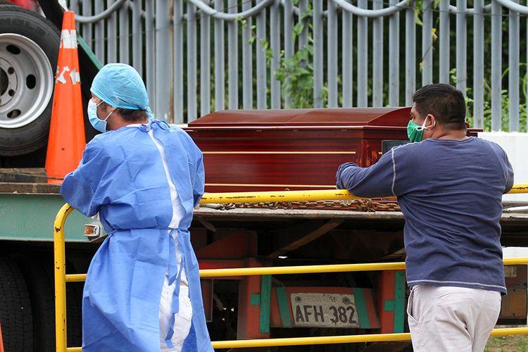 Seorang pria dengan masker wajah (kanan) menunggu jenazah kerabatnya, di sebelah seorang petugas di luar sebuah rumah sakit di Guayaquil, Ekuador, Rabu (1/4/2020). Otoritas Ekuador dalam beberapa hari terakhir telah mengumpulkan setidaknya 150 jenazah dari jalan-jalan dan rumah para warga di Kota Guayaquil, di tengah lonjakan kasus virus corona di wilayah tersebut.