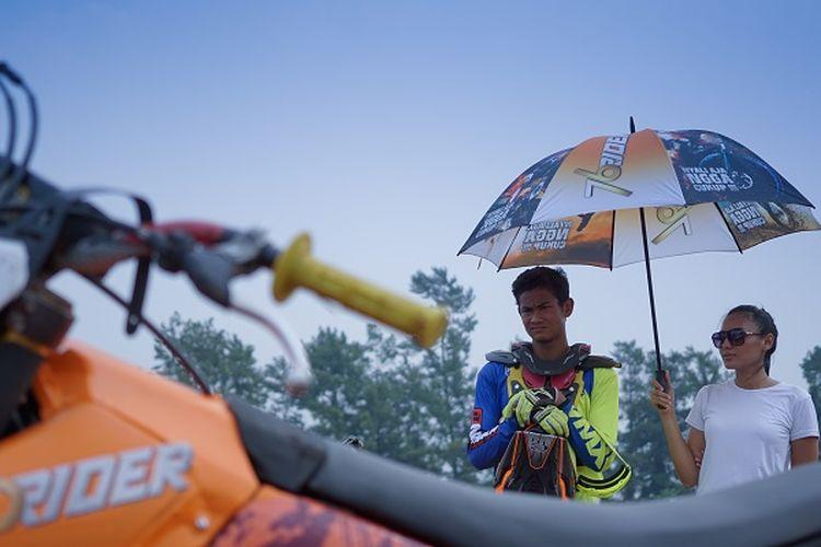 Kroser sekaligus freestyle motocross Zulmi Aristiawan sedang dipayungi umbrella girl di Sirkuit Paramount, Bumi Serpong Damai, Tangerang, Banten, ketika melakukan syuting TVC 76 Rider.