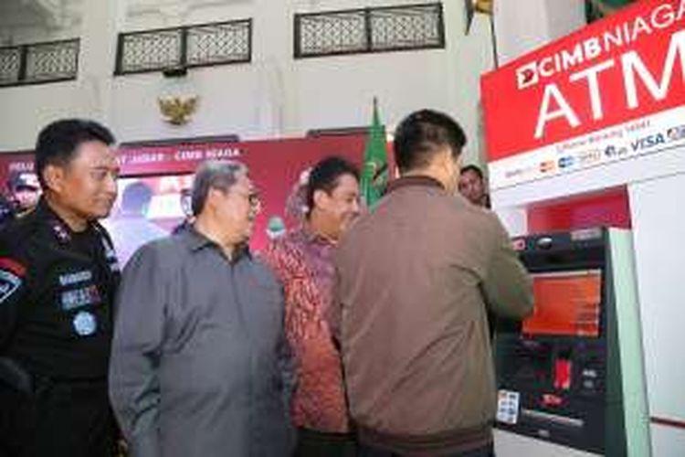 Gubernur Jawa Barat Ahmad Heryawan (kedua dari kiri) bersama Kapolda Jawa Barat Irjen Pol. Bambang Waskito (kiri), dan Head of Digital Banking, Branchless and Partnership CIMB Niaga Bambang Karsono Adi (kedua dari kanan) menyaksikan nasabah melakukan pembayaran pajak kendaraan bermotor (PKB) melalui ATM CIMB Niaga.